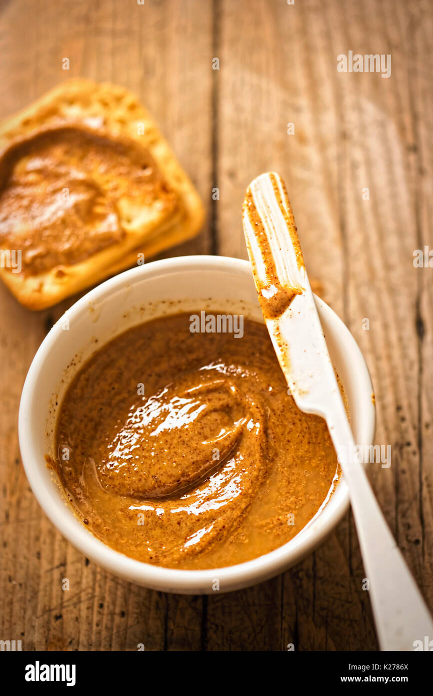 Almond butter in bowl with crackers on wooden table - Stock Image