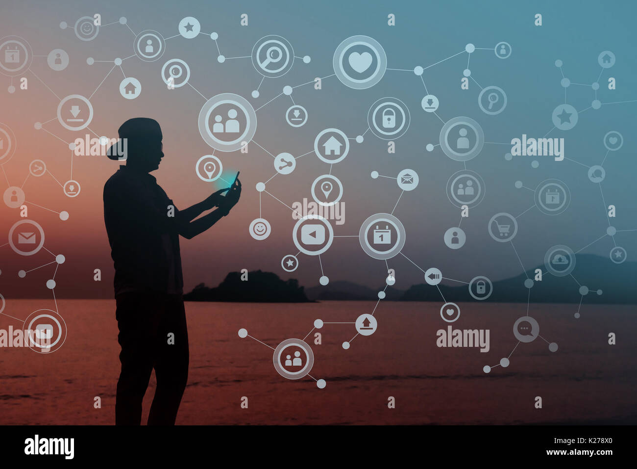 Always Connected concept, Silhouette of Young human using smart phone to Communicate in Network, Beach or Countryside as background - Stock Image