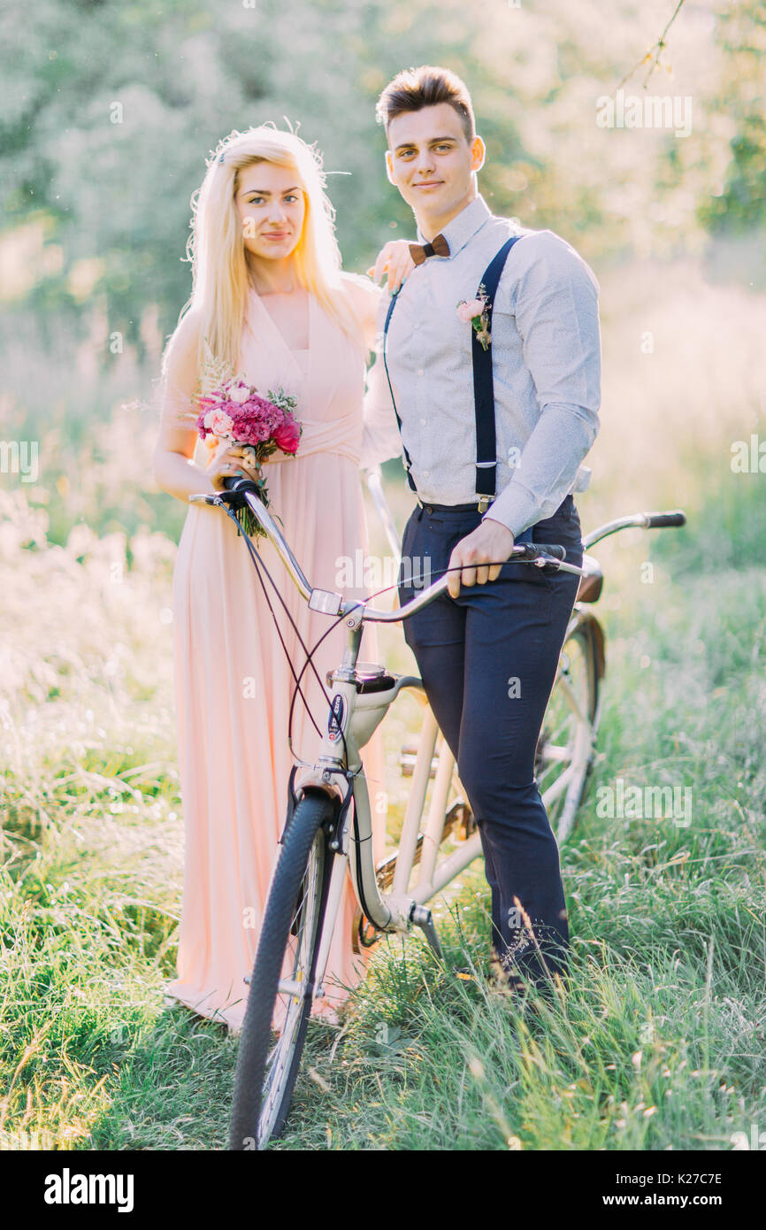 The cute vertical portrait of the bridesmaid holding the pink bouquet and the best man in the blue suit carrying Stock Photo