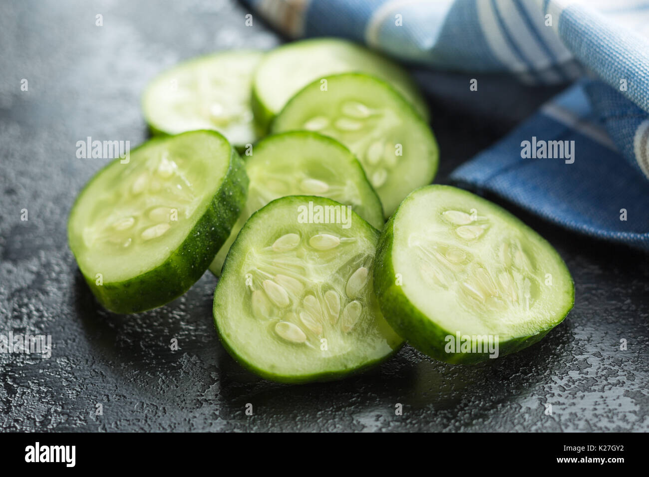 Sliced green cucumbers. Cucumber slices on black table. - Stock Image