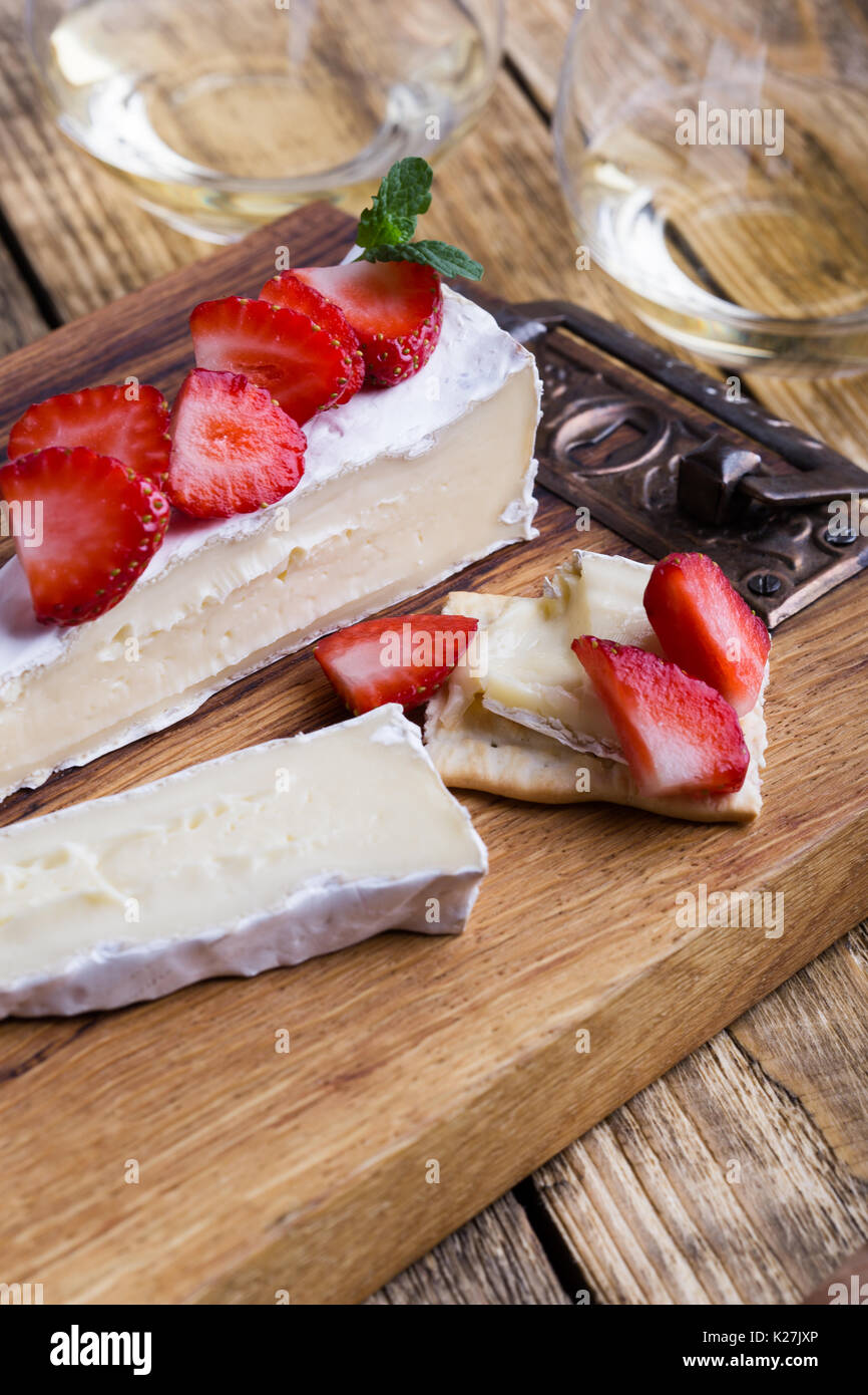Cheese platter. Brie with fresh strawberries and mint on rustic wooden board - Stock Image