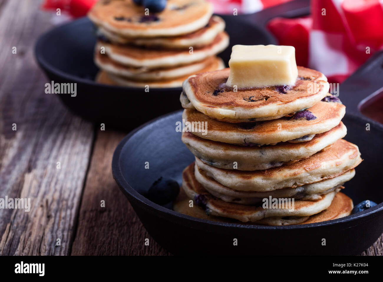 Pancakes with fresh blueberries topped with butter in cast iron skillet served for romantic brunch on rustic table - Stock Image