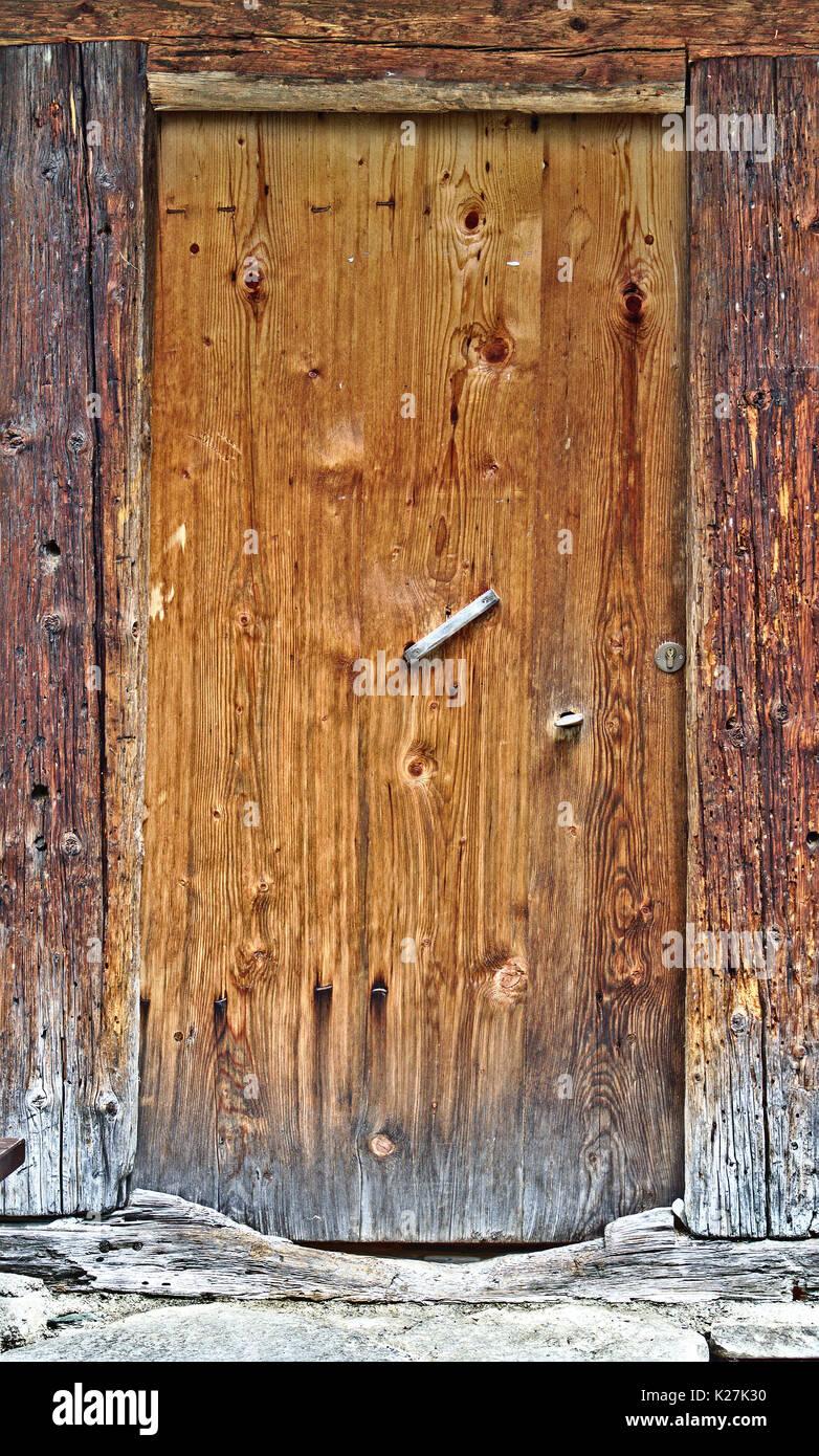 Old wooden door with big cracked wooden door frame - Stock Image