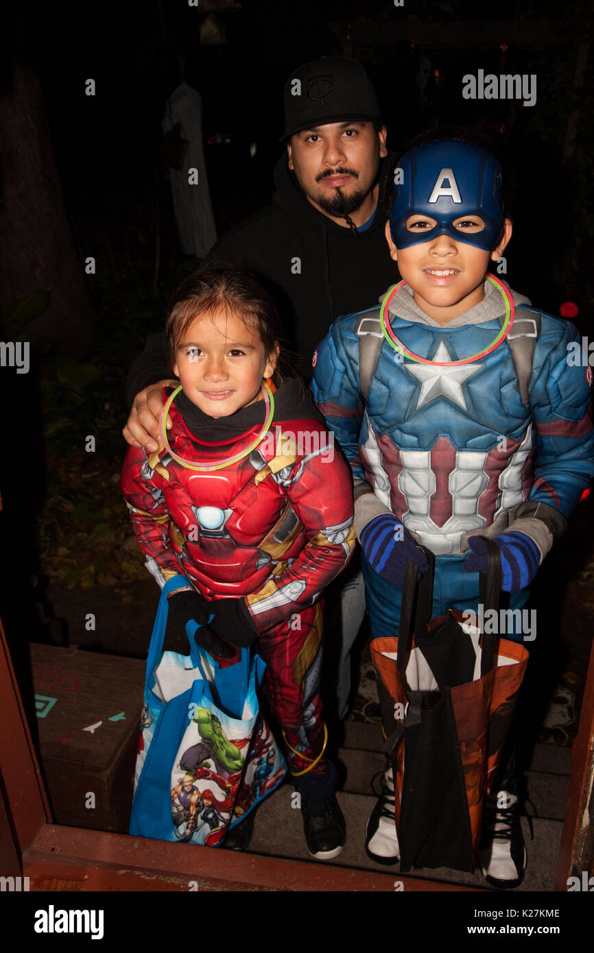 Boys in Halloween Superheros Captain America and Power Ranger costumes trick and treating with dad. St Paul Minnesota MN USA - Stock Image