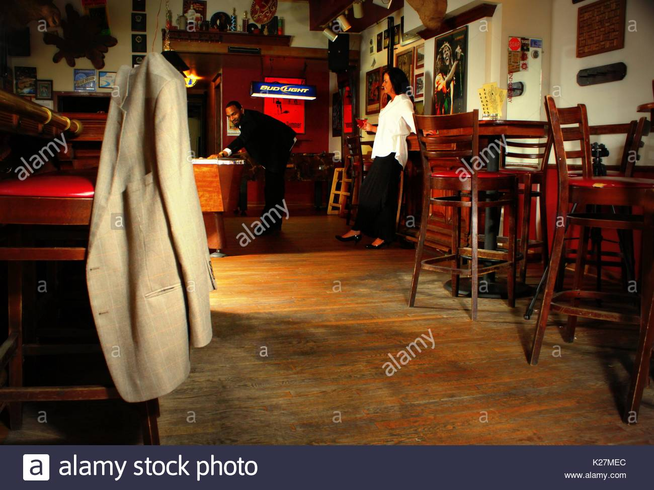 Suit jacket hanging on the back of a bar chair (as if left behind) - Stock Image
