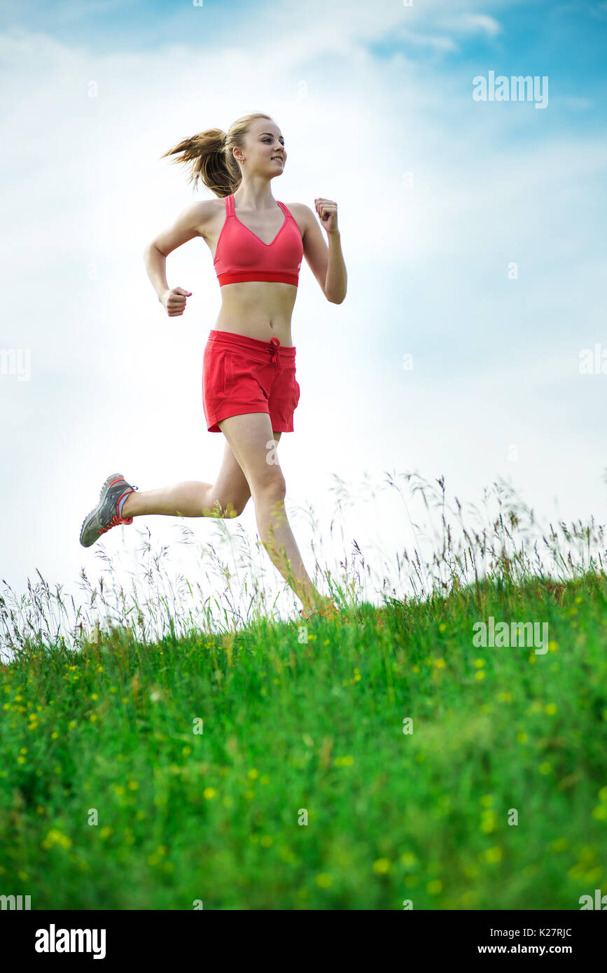Young woman running summer park rural road. Outdoor exercises. J - Stock Image