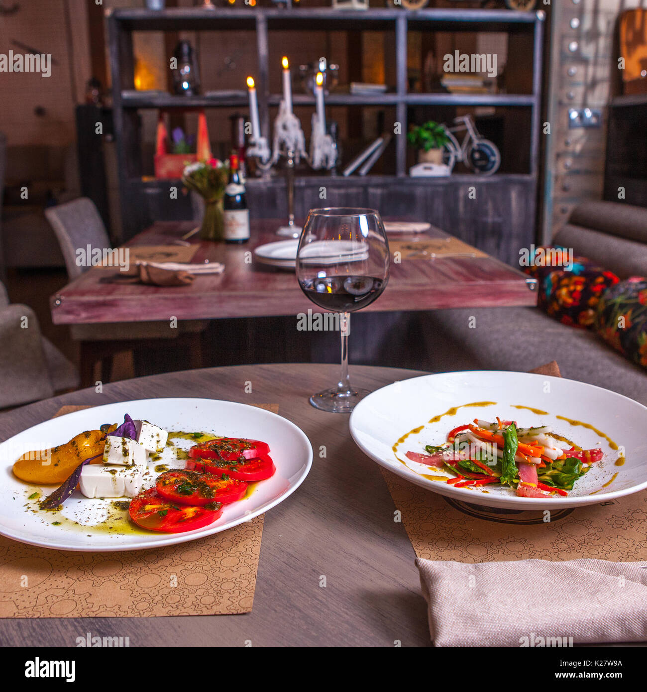 two plates with vegetarian salads on the table in the restaurant - Stock Image