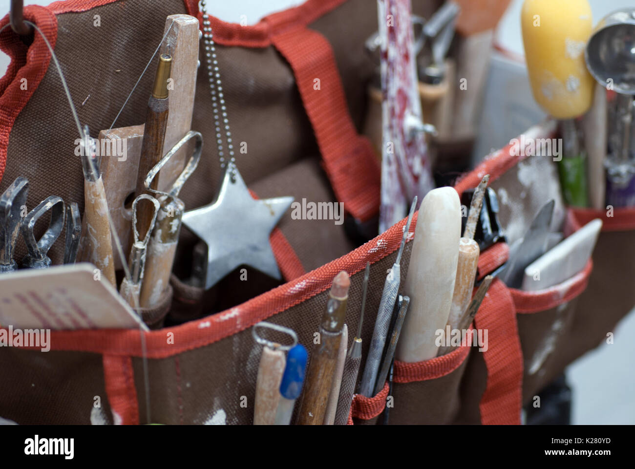 Artist tote organizer filled with pottery tools - Stock Image