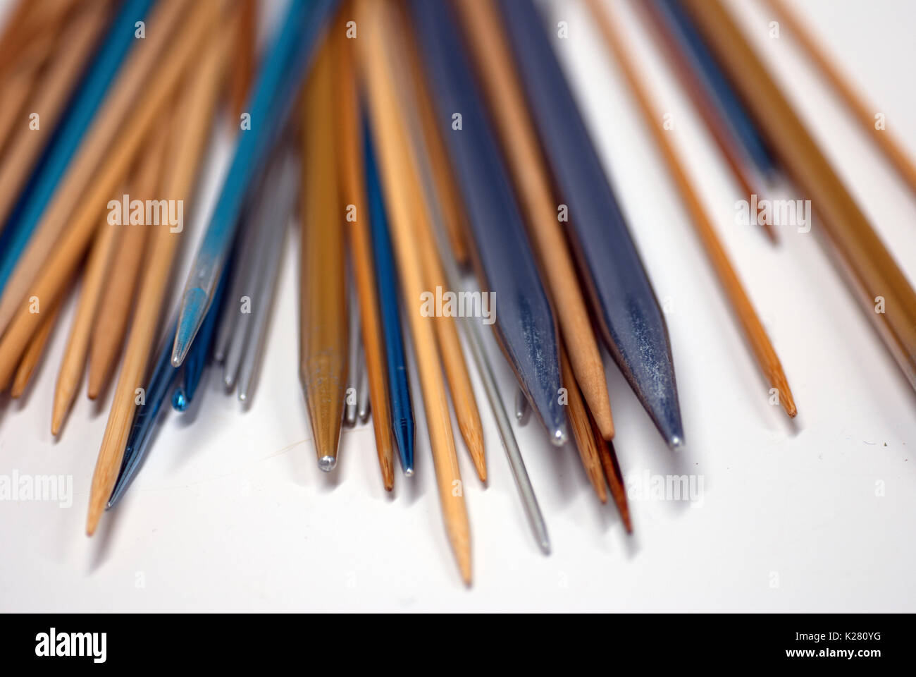 Collection of knitting needles on a white background - Stock Image