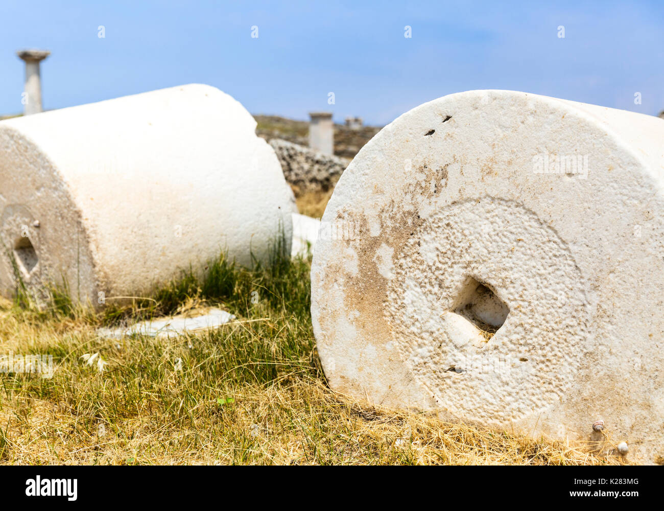 Cylindrical column blocks lying amidst the ancient ruins of Delos, Greece. - Stock Image