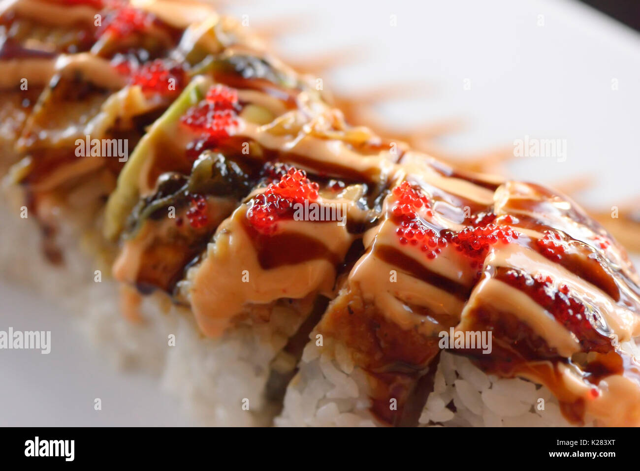 Artistic closeup of sushi red dragon roll with salmon and caviar - Stock Image