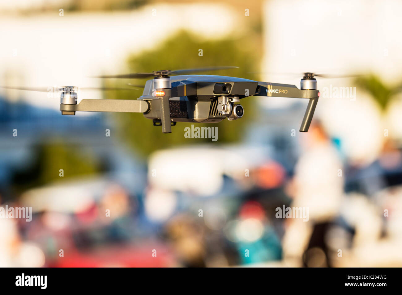 Mavic Pro quadcopter drone flying over people. - Stock Image