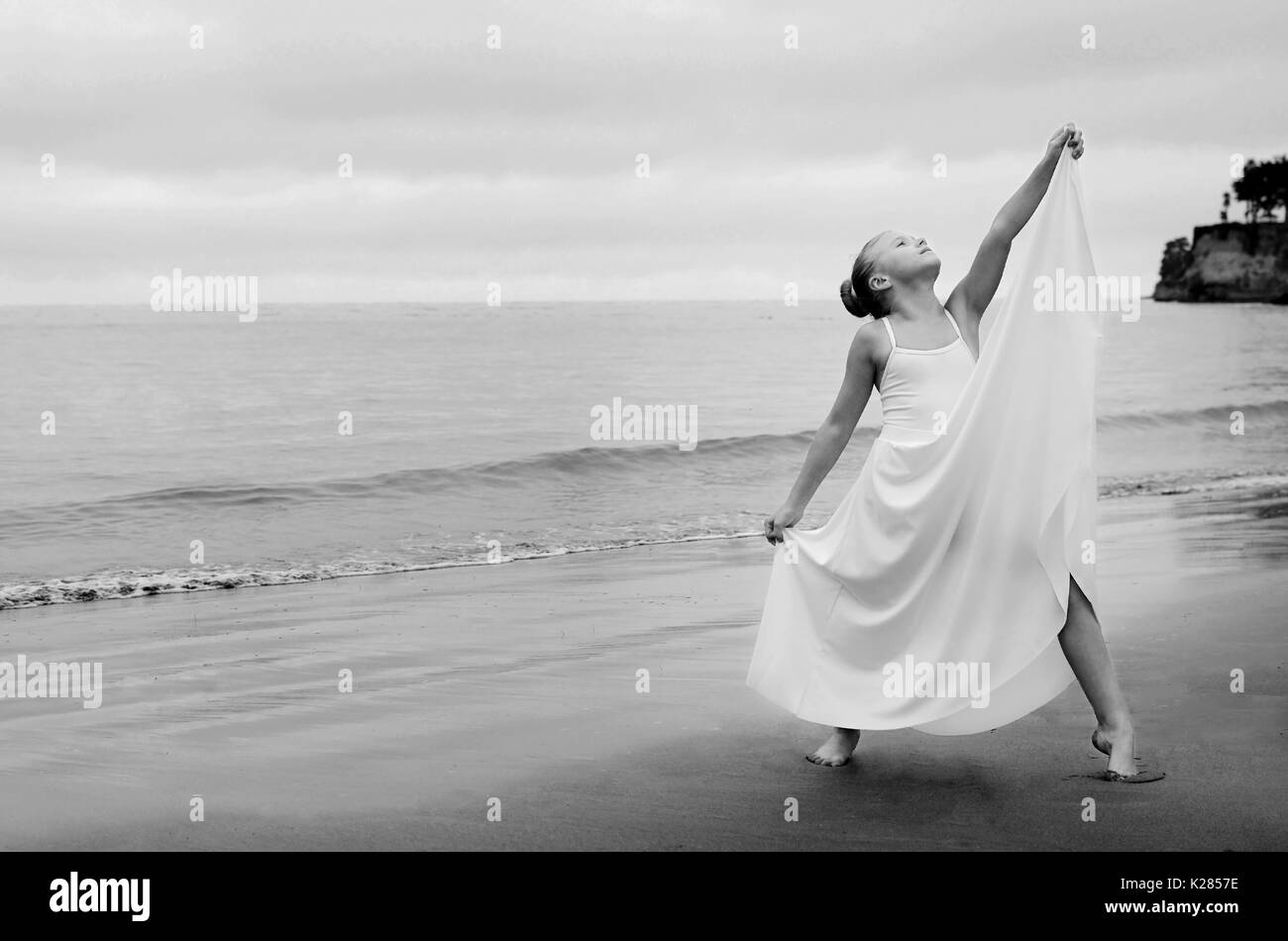 Small dancer strikes a pose on beach - Stock Image
