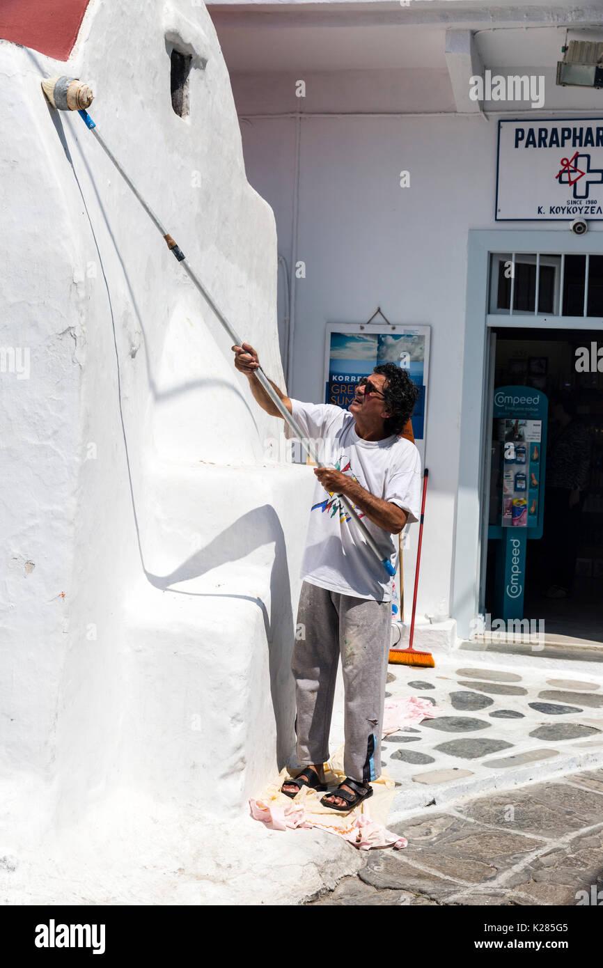 A man busy whitewashing a church wall, Mykonos, Greece. Stock Photo
