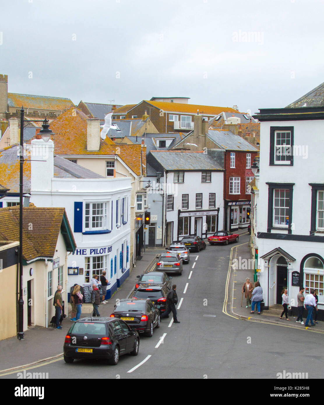 Traffic congestion with row of cars at red traffic lights in narrow street between high buildings in Lyme Regis, West Dorset, England - Stock Image
