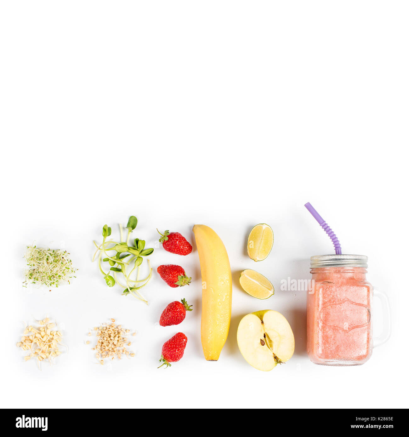 Detox cleanse drink, fruits and berries smoothie ingredients. Natural, organic healthy juice for weight loss diet or fasting day. Mason jar of dietary drink with strawberries, microgreens and banana - Stock Image