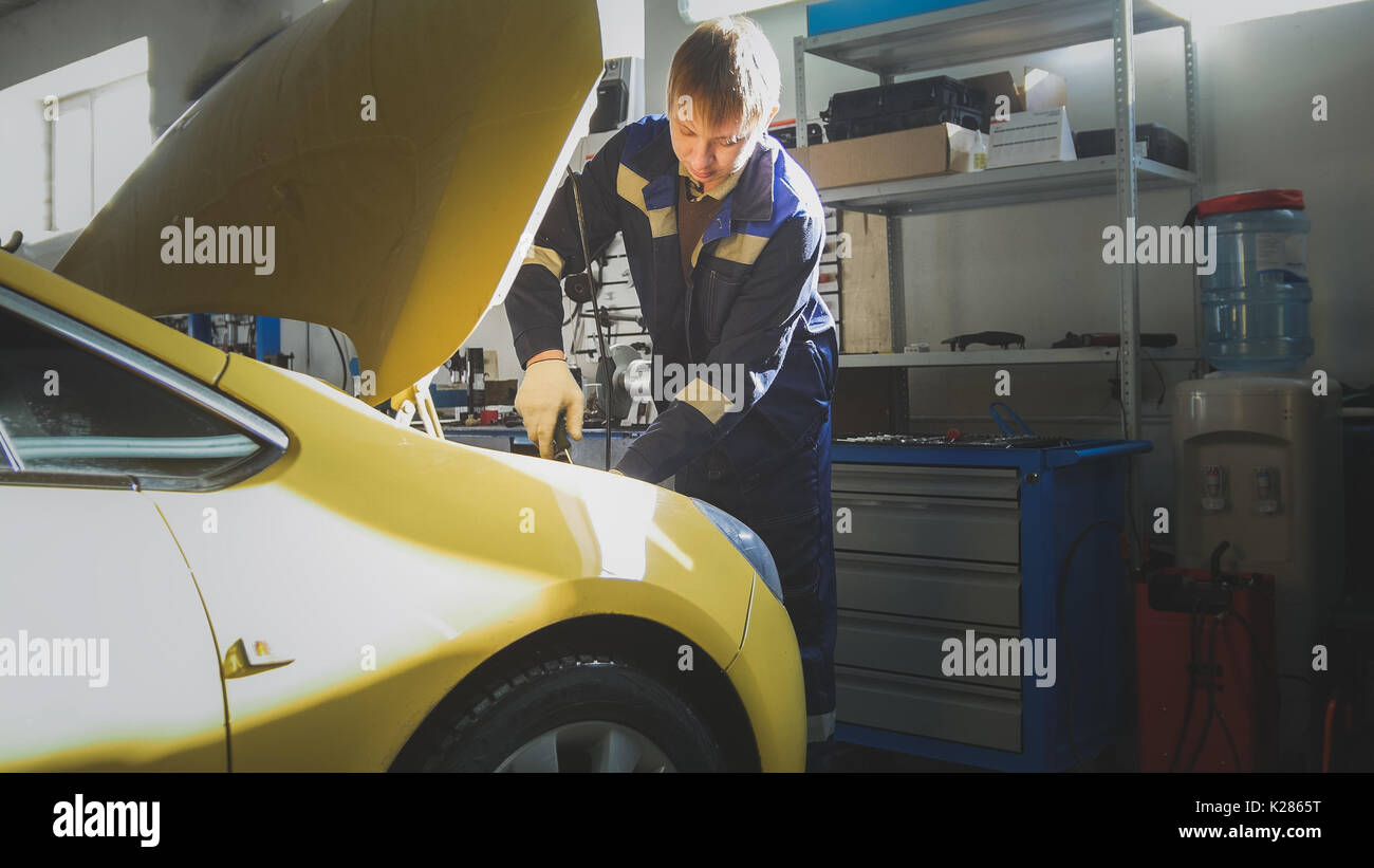 Automobile service - mechanic unscrews detail of car in hood, slider - Stock Image
