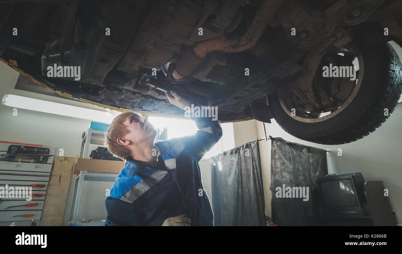 Mechanical workshop - a mechanic checks the suspension of car, wide angle - Stock Image