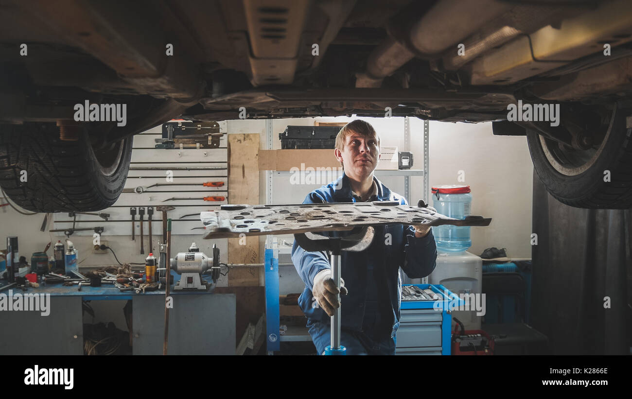 Male caucasian worker - mechanic in automobile garage repairing workshop - under lifted car - Stock Image