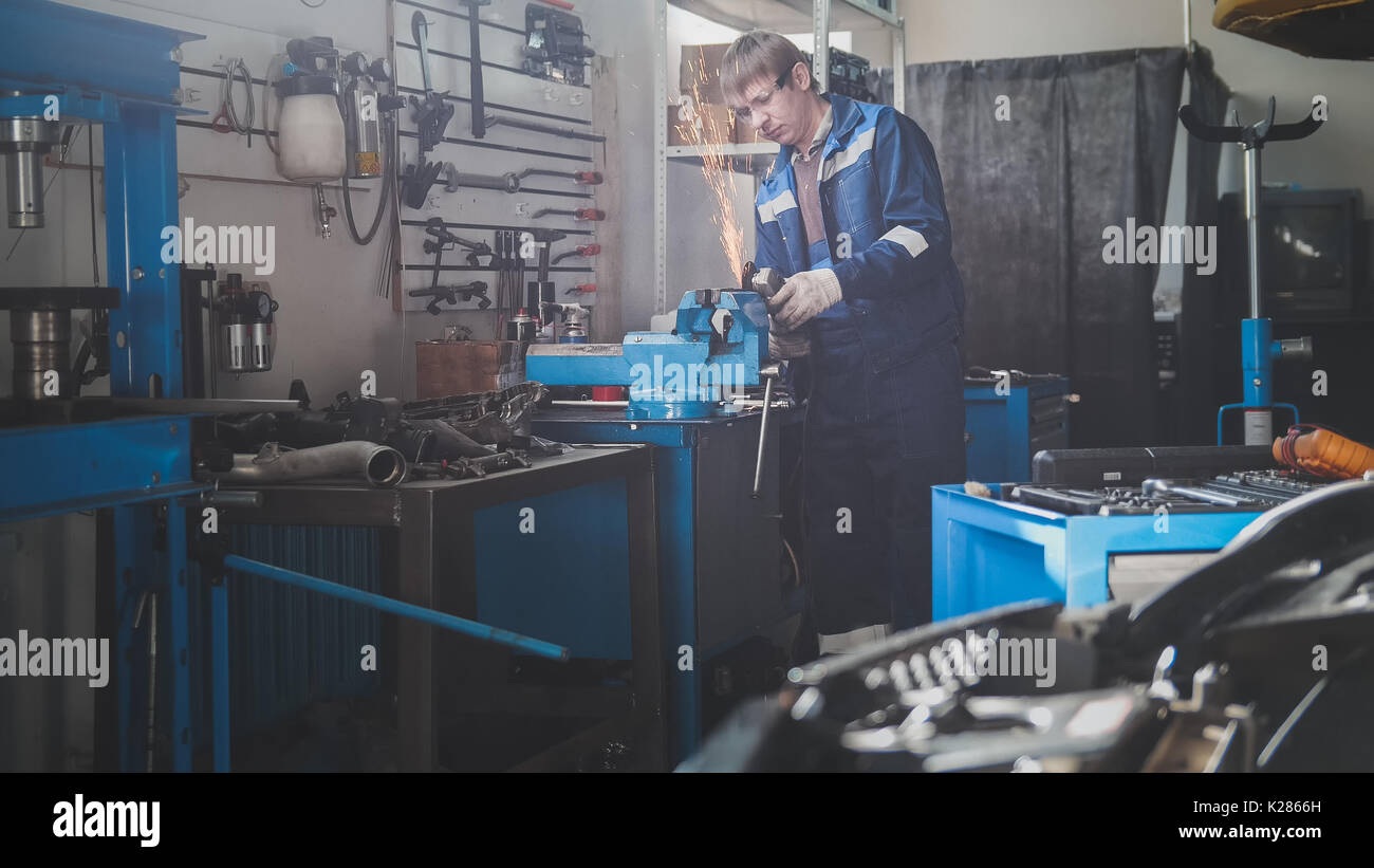 Car auto workshop - grinding metal construction in - sparks of circular saw - Stock Image