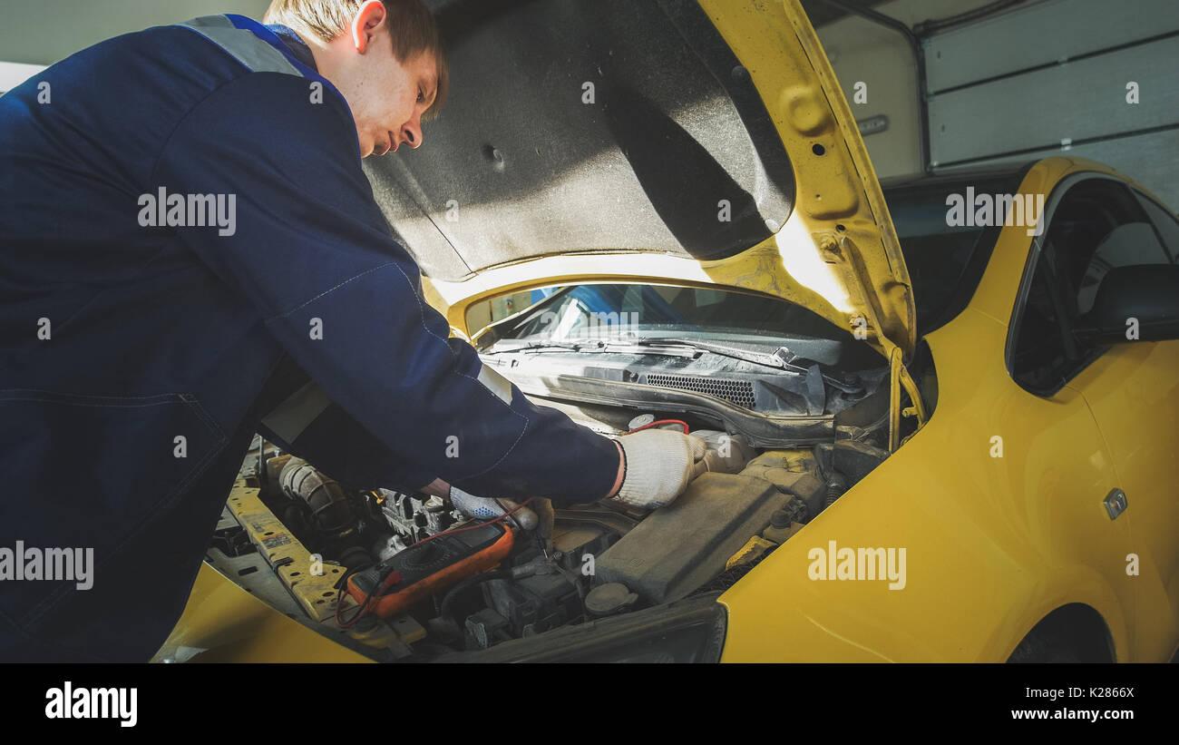 Mechanic in car repairing service - diagnostics in engine compartment - Stock Image