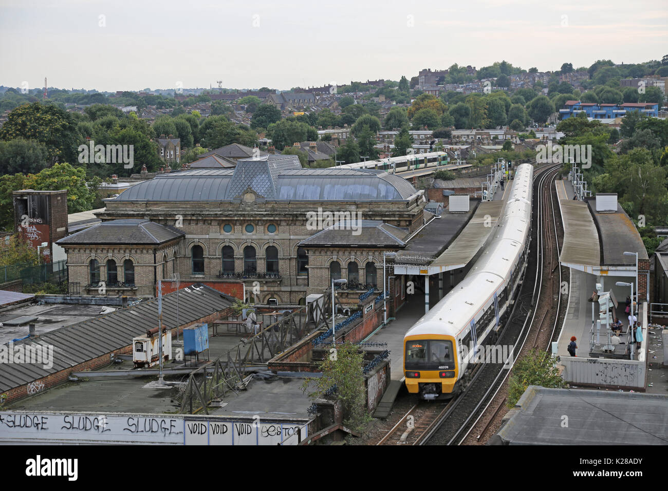 High level view of Peckham Rye Station in Southeast London, UK. Shows Southeastern network train at Platform 3 and the Victorian station building. - Stock Image