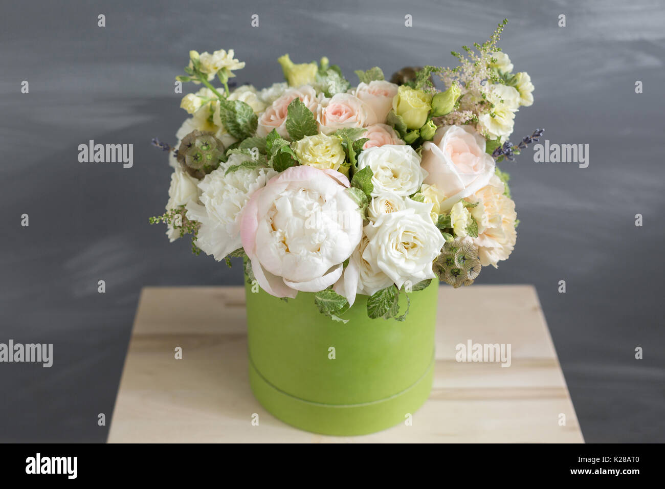 Beautiful tender bouquet of flowers in green box on gray background with space for text - Stock Image