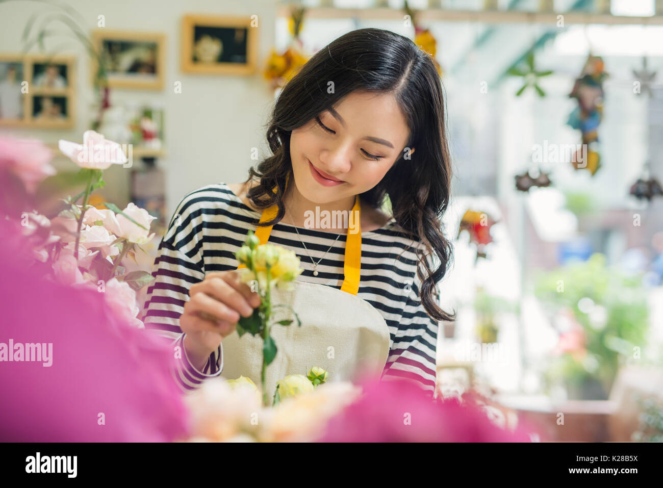 Pretty young florist with bouquet in flower shop - Stock Image
