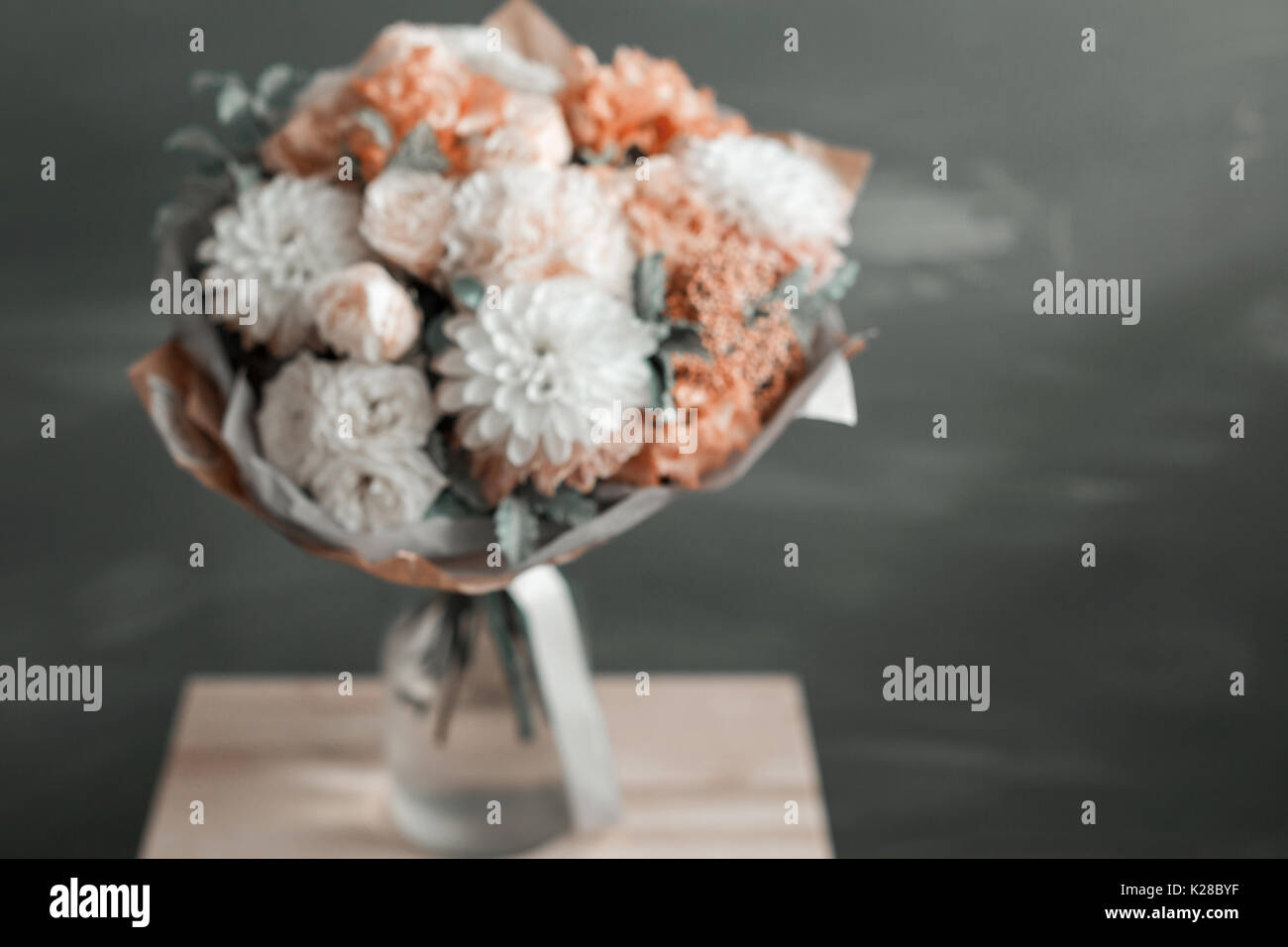 abtract Blur. Bouquet in kraft paper. A simple bouquet of flowers and greens - Stock Image