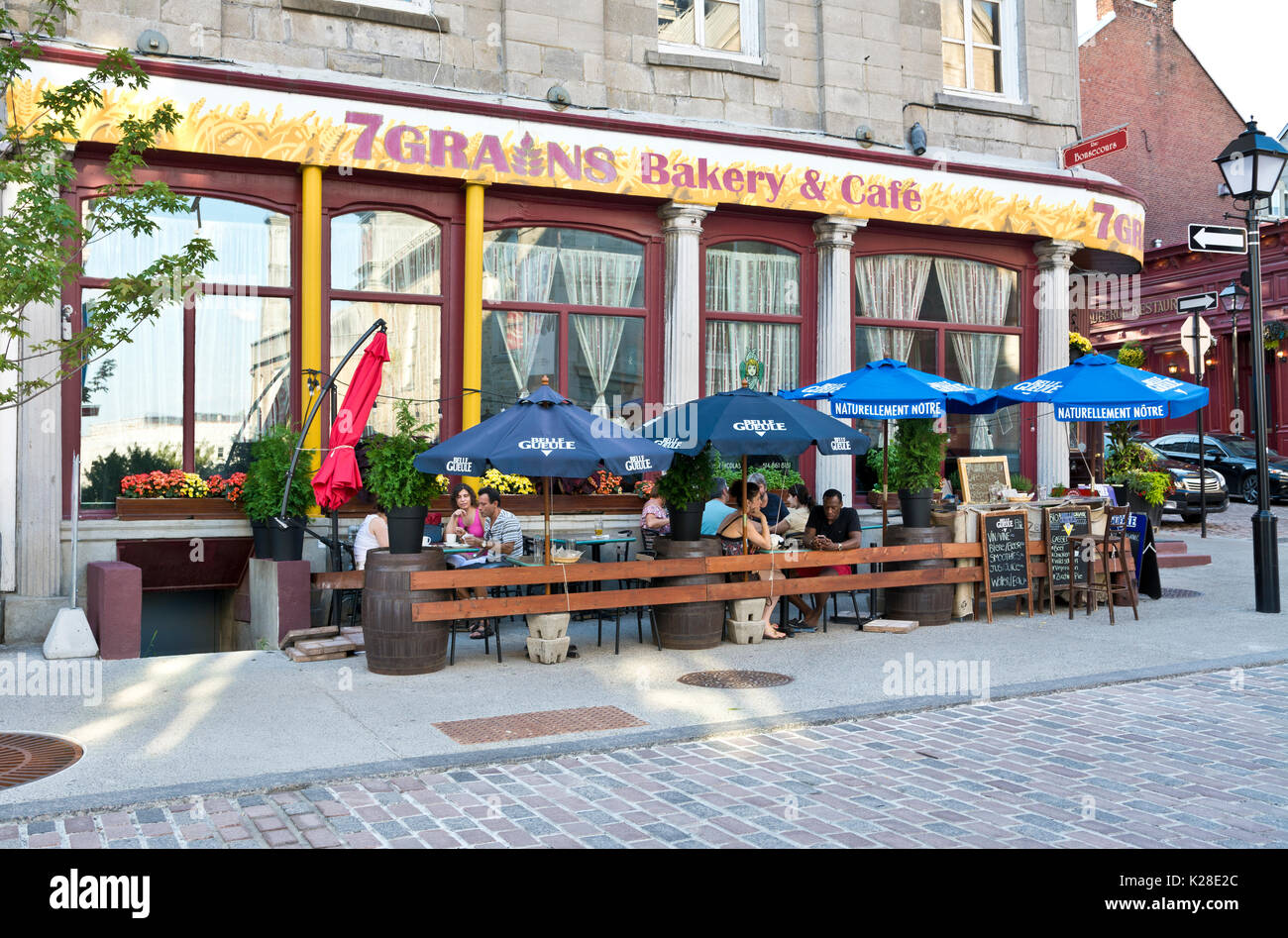 People on the patio at 7 Grains Bakery & Cafe in Old Montreal. - Stock Image