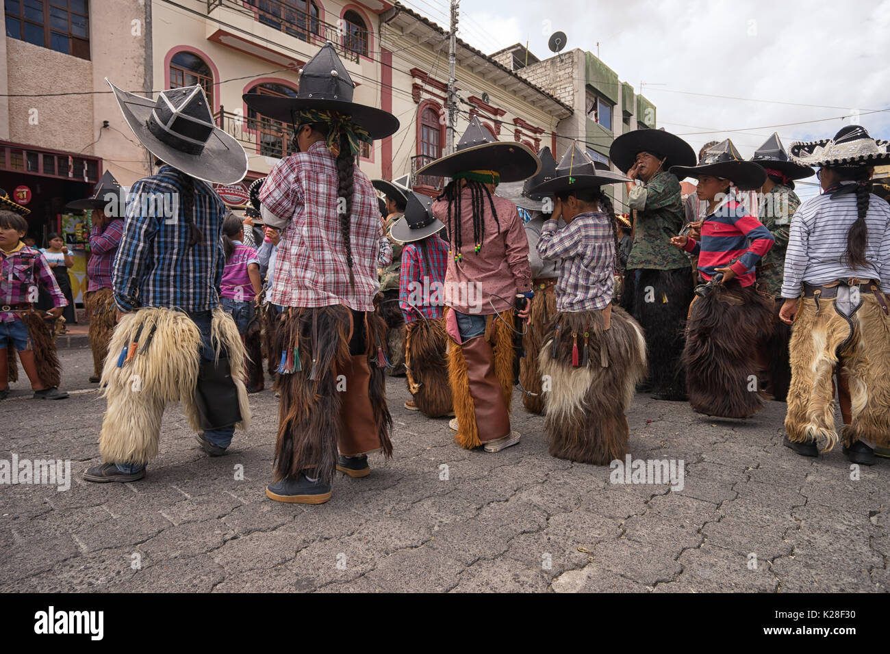 June 25, 2017 Cotacachi, Ecuador: children wearing sombreros and chaps athe the Inti Raymi celebrations - Stock Image