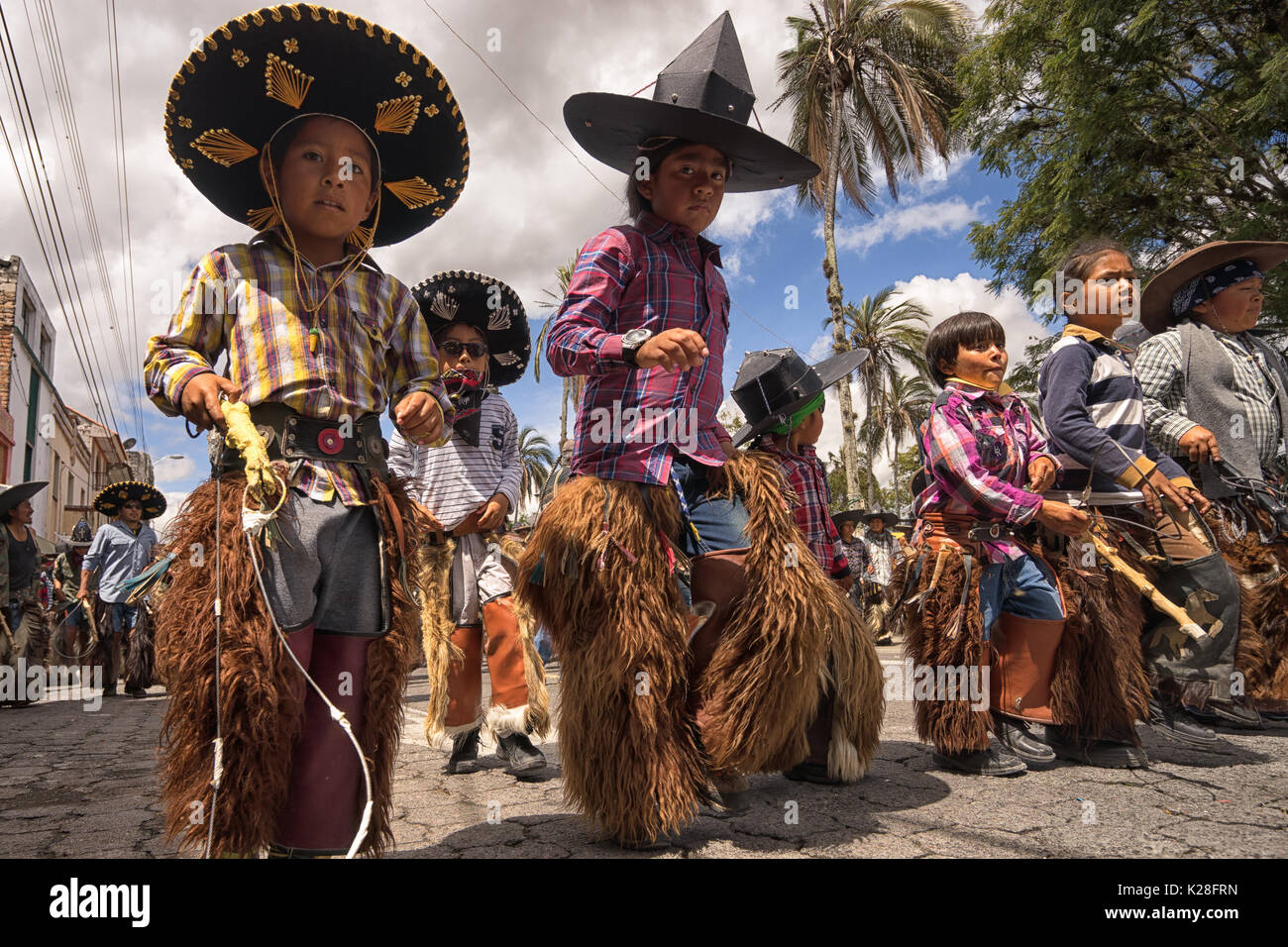 June 25, 2017 Cotacachi, Ecuador: children wearing sombreros and chaps at the Inti Raymi celebrations - Stock Image