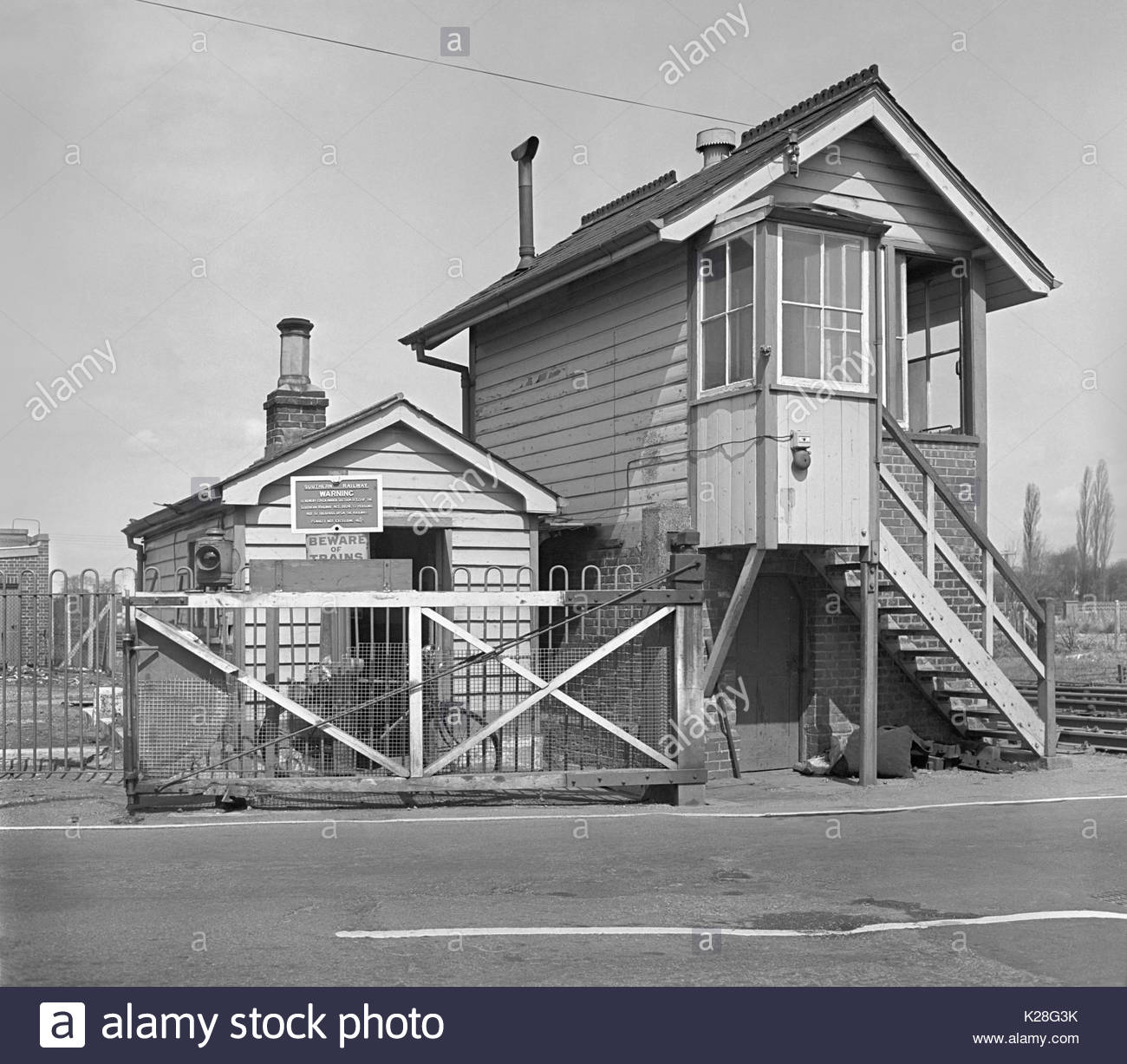 Signal Box and level crossing at North Camp railway station, Farnborough,Hampshire, England, UK on the British Rail line between Reading and Guildford – level crossing gates opened outwards – 1960s (1968) - Stock Image