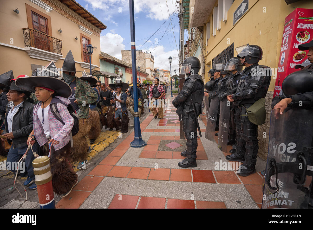 June 25, 2017 Cotacachi, Ecuador: riot police standing by as the male dances run down the street towards the main plaza - Stock Image