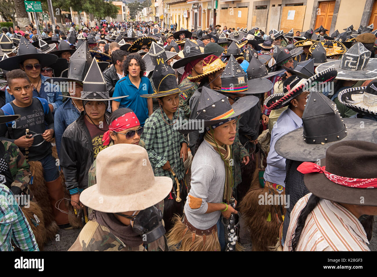 June 25, 2017 Cotacachi, Ecuador: male indigenous dancers in a compact formation during the 'occupy the plaza' parade during Inti Raymi - Stock Image