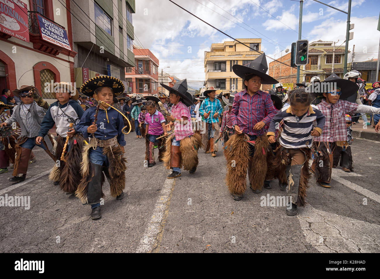 June 25, 2017 Cotacachi, Ecuador: indigenous quechua children wearing sombreros and chaps dancing at the Inti Raymi celebrations - Stock Image
