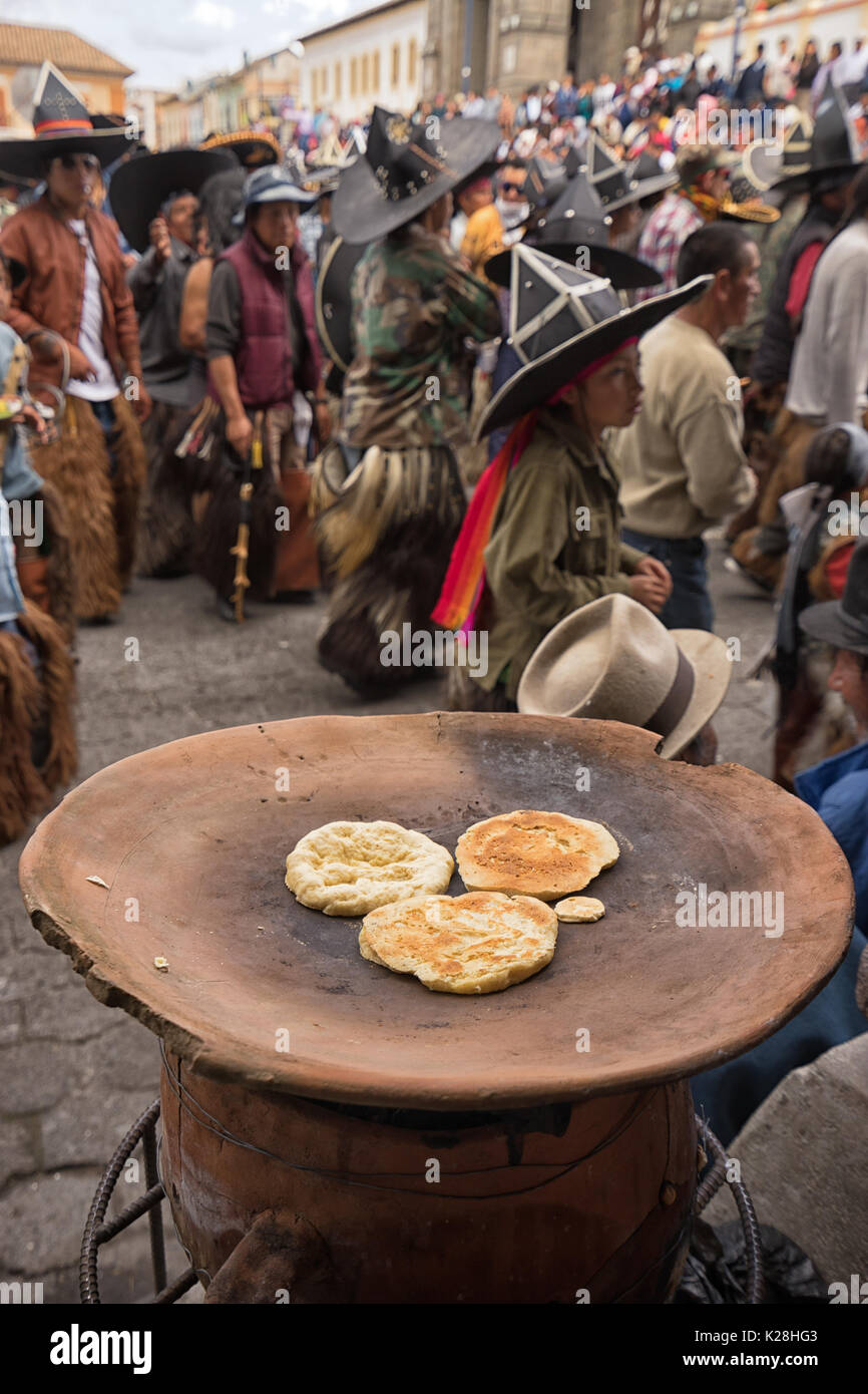June 25, 2017 Cotacachi, Ecuador: corn based flat bread is being prepared by the side of the street on clay platter heated by wood fire at the Intin R - Stock Image