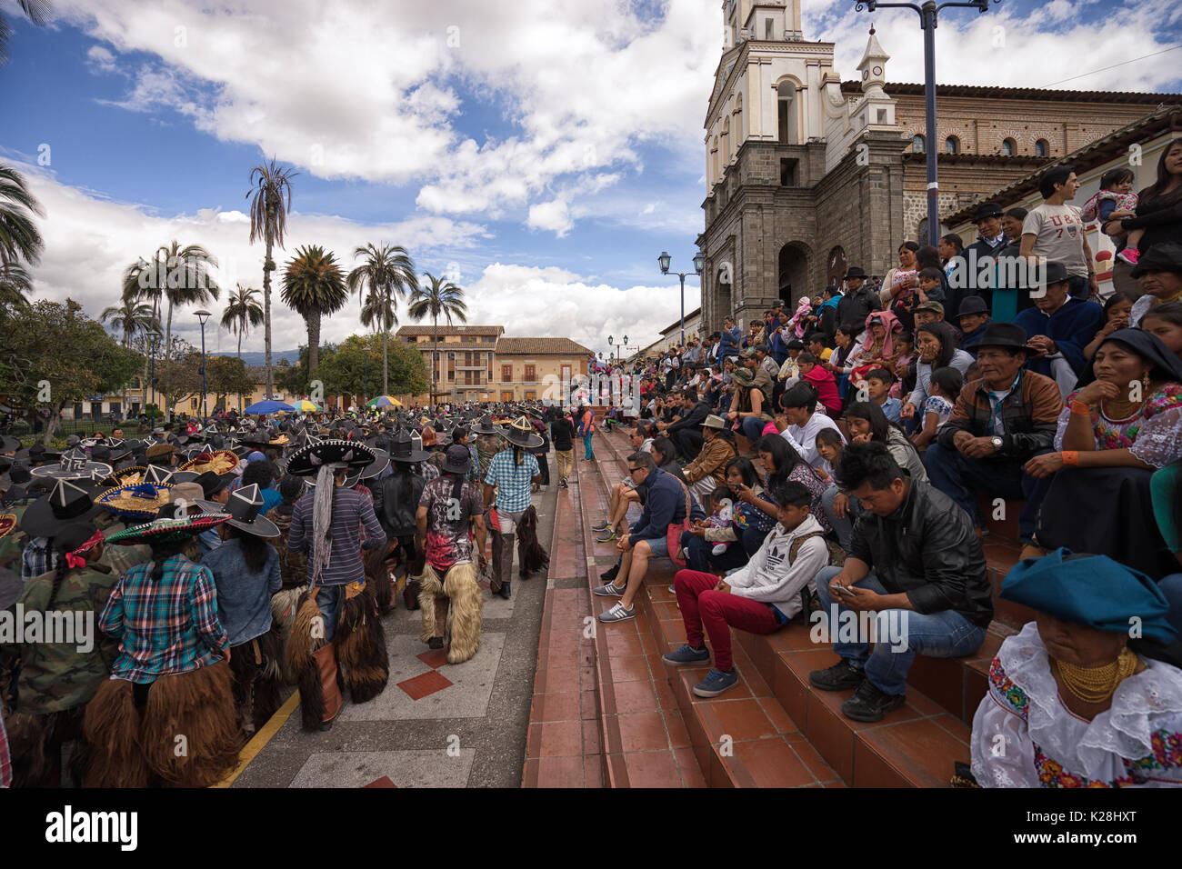 June 25, 2017 Cotacachi, Ecuador: spectators stting on the stairs of the church in the main plaza watching the Inti Raymi parade - Stock Image