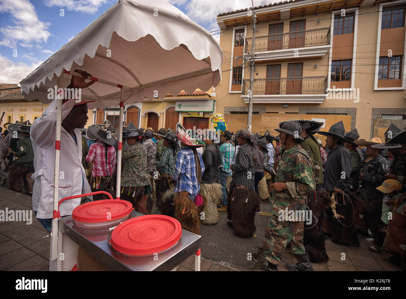June 25, 2017 Cotacachi, Ecuador: a street food vendor watching the Inti Raymi parade from the sidewalk - Stock Image