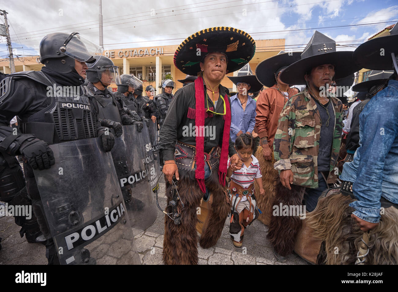 June 25, 2017 Cotacachi, Ecuador: police closing off access to a street during Inti Raymi parade to separate the male dancer groups and avoid violence - Stock Image