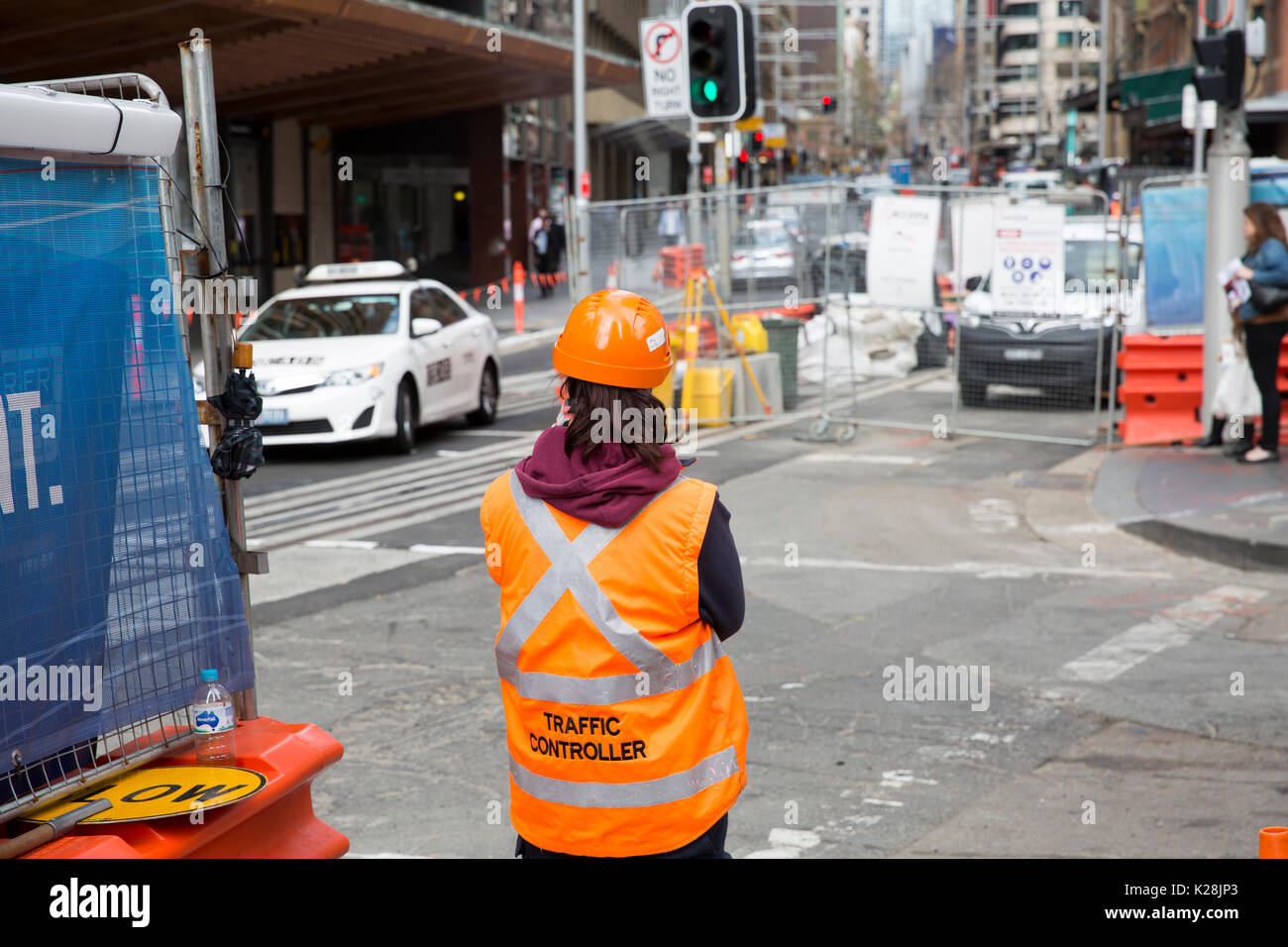 Lady girl working as a traffic controller in Sydney on the CBD light rail project, typically backpackers occupy these jobs on a visa, Sydney,Australia - Stock Image