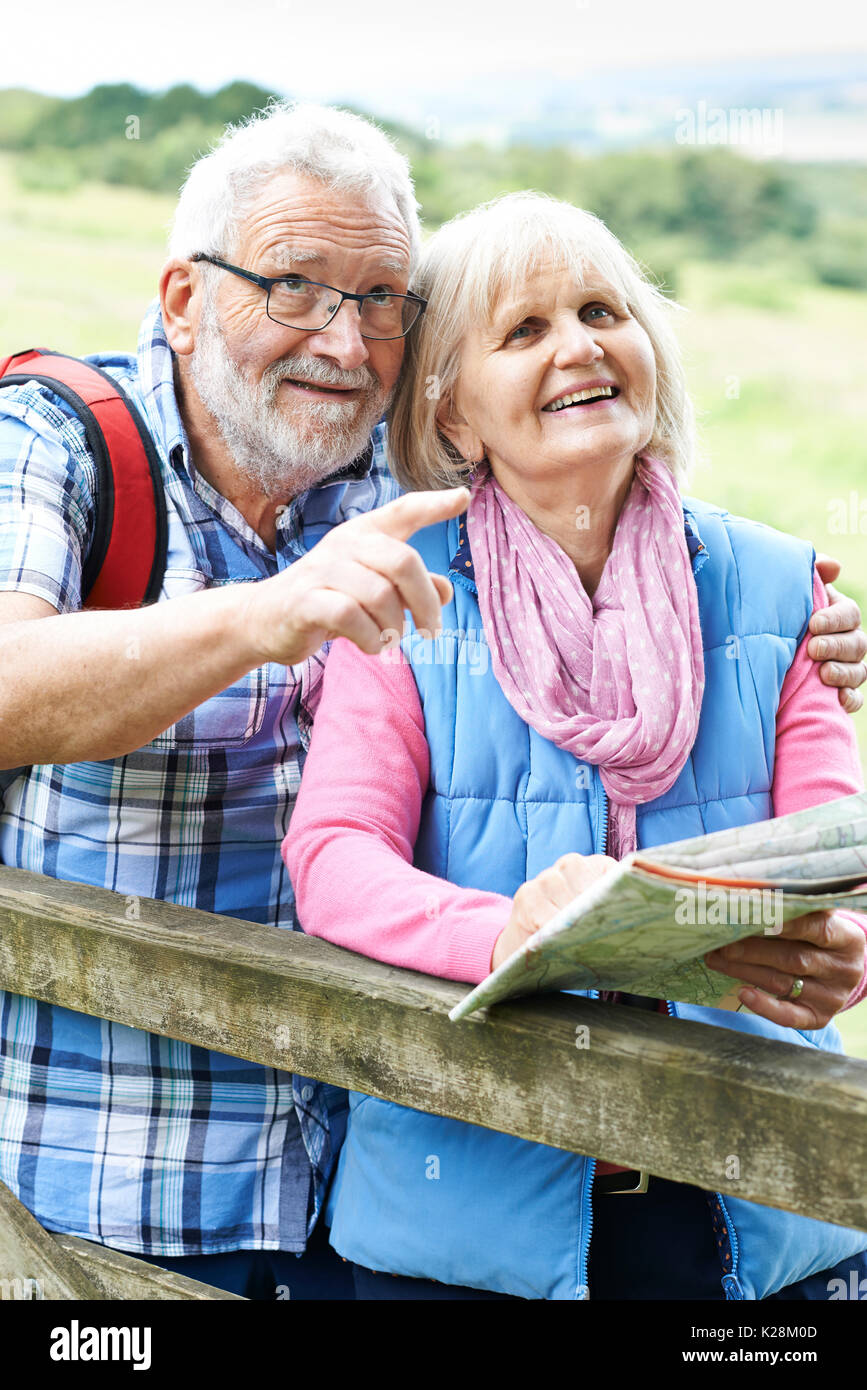 Senior Couple Hiking In Countryside With Map - Stock Image
