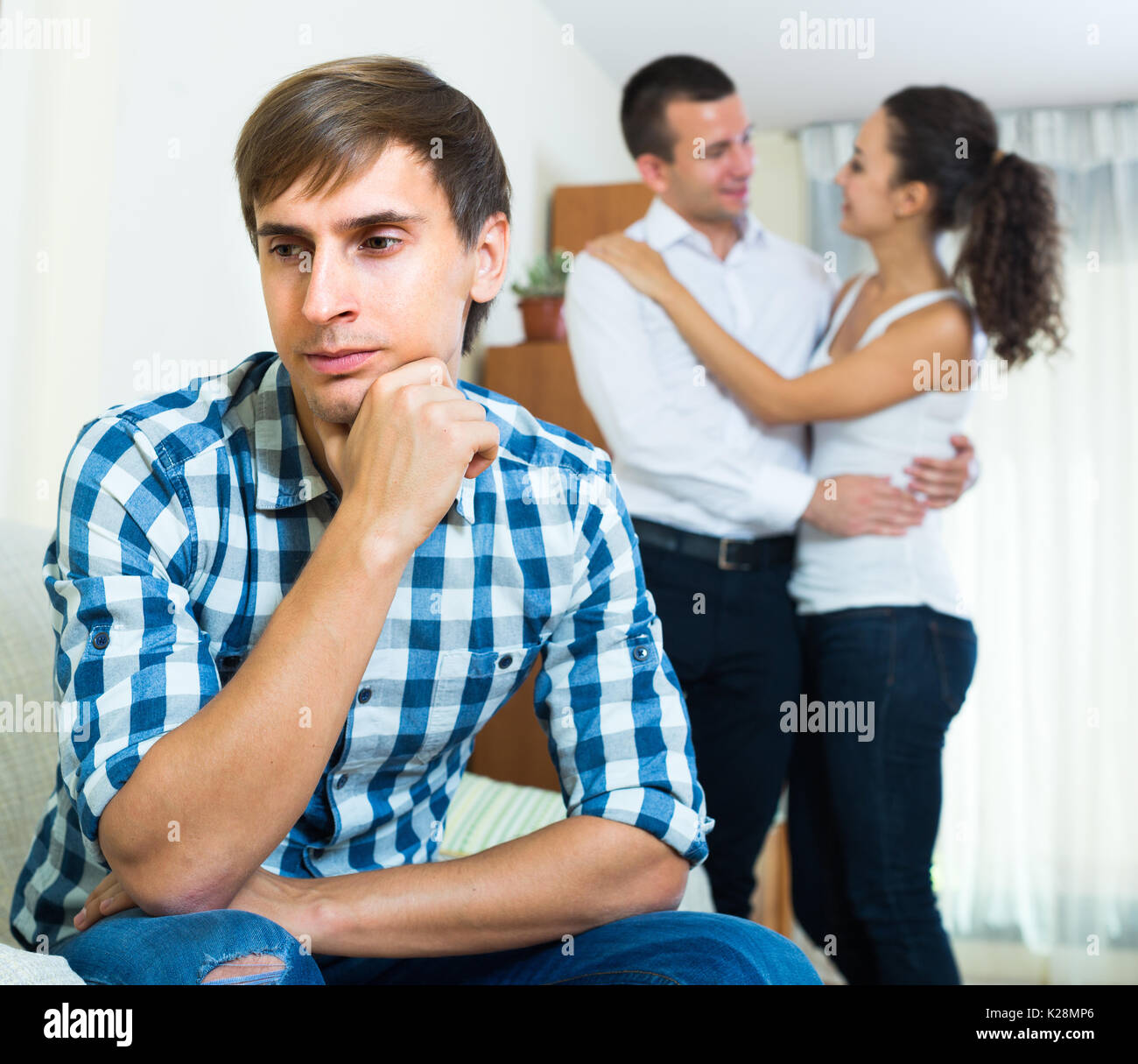 Man suffering in love triangle: young woman prefers another guy - Stock Image