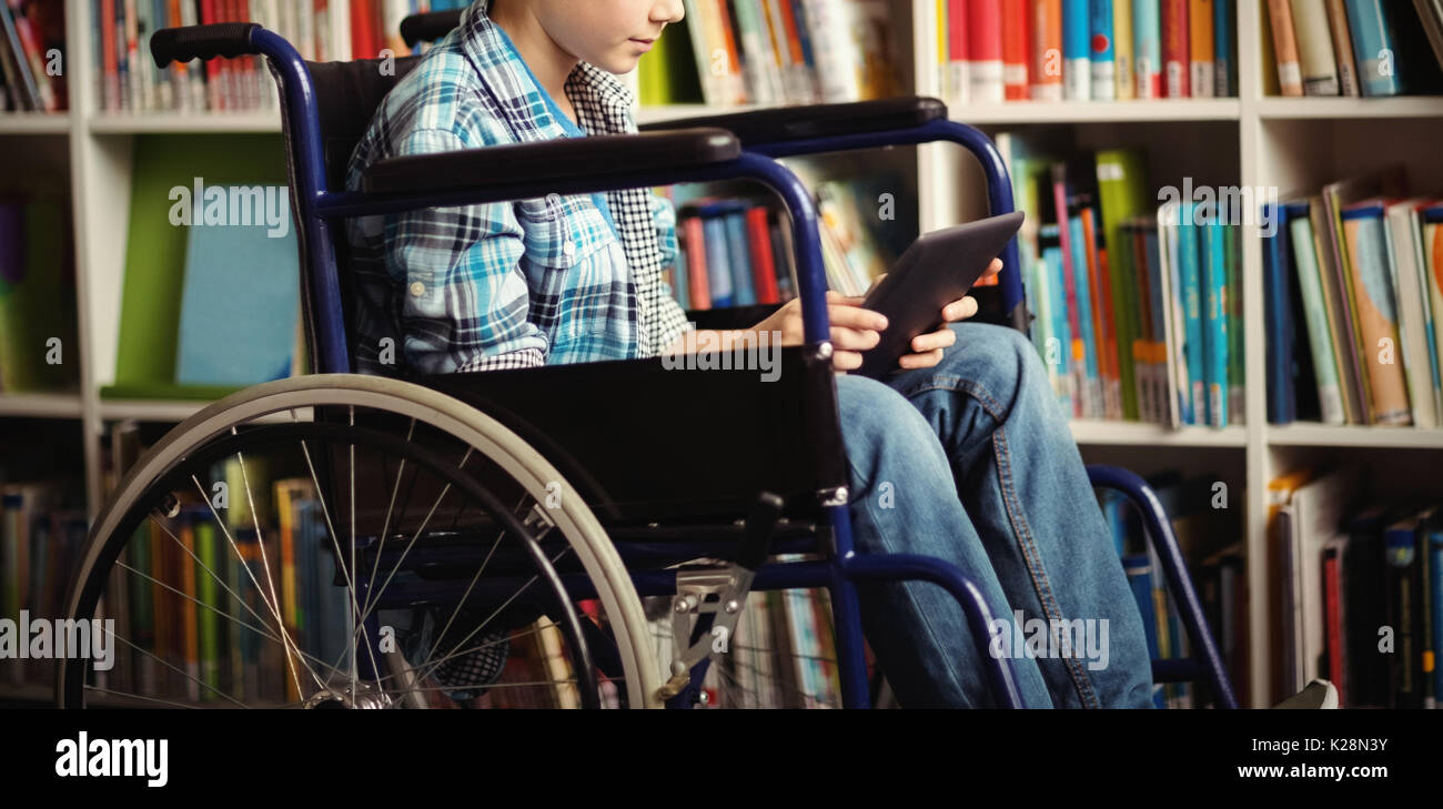 Disabled schoolboy using digital tablet in library - Stock Image