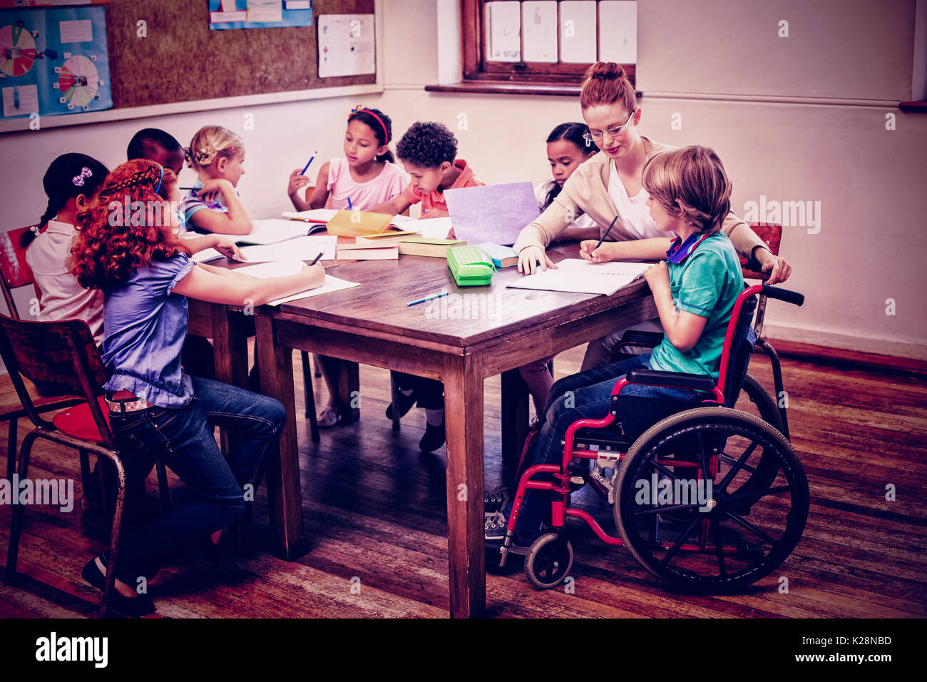 Pretty teacher helping pupils in classroom - Stock Image