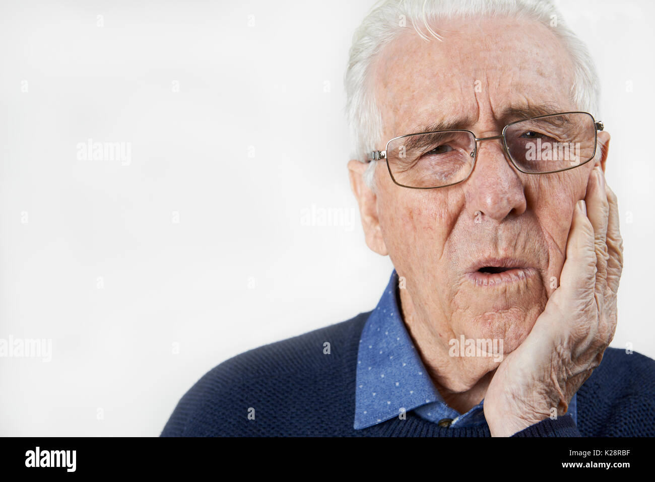 Studio Portrait Of Senior Man Suffering With Toothache - Stock Image