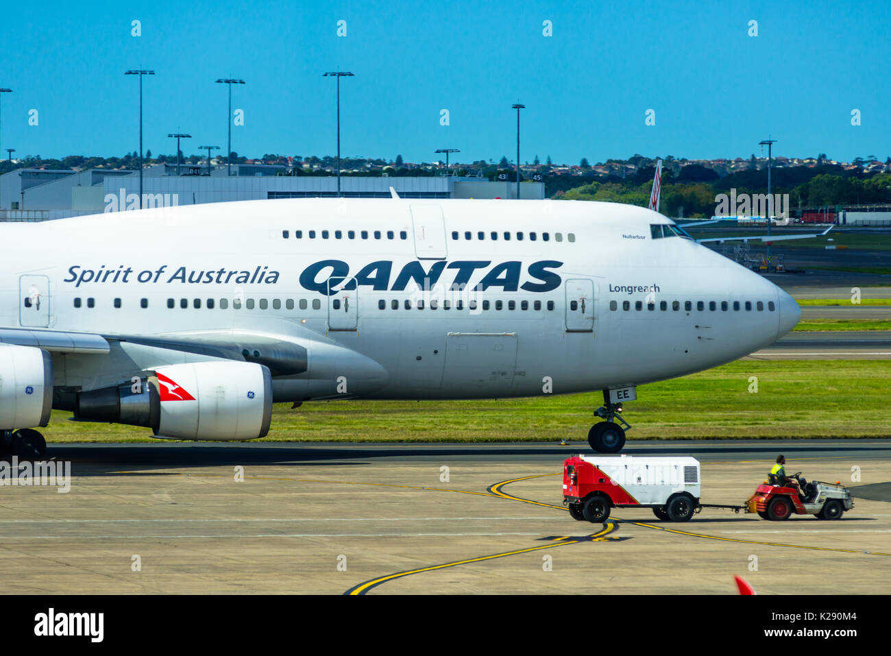 A Qantas 747 jumbo jet next to a baggage vehicle at Sydney international airport, New South Wales, Australia. - Stock Image