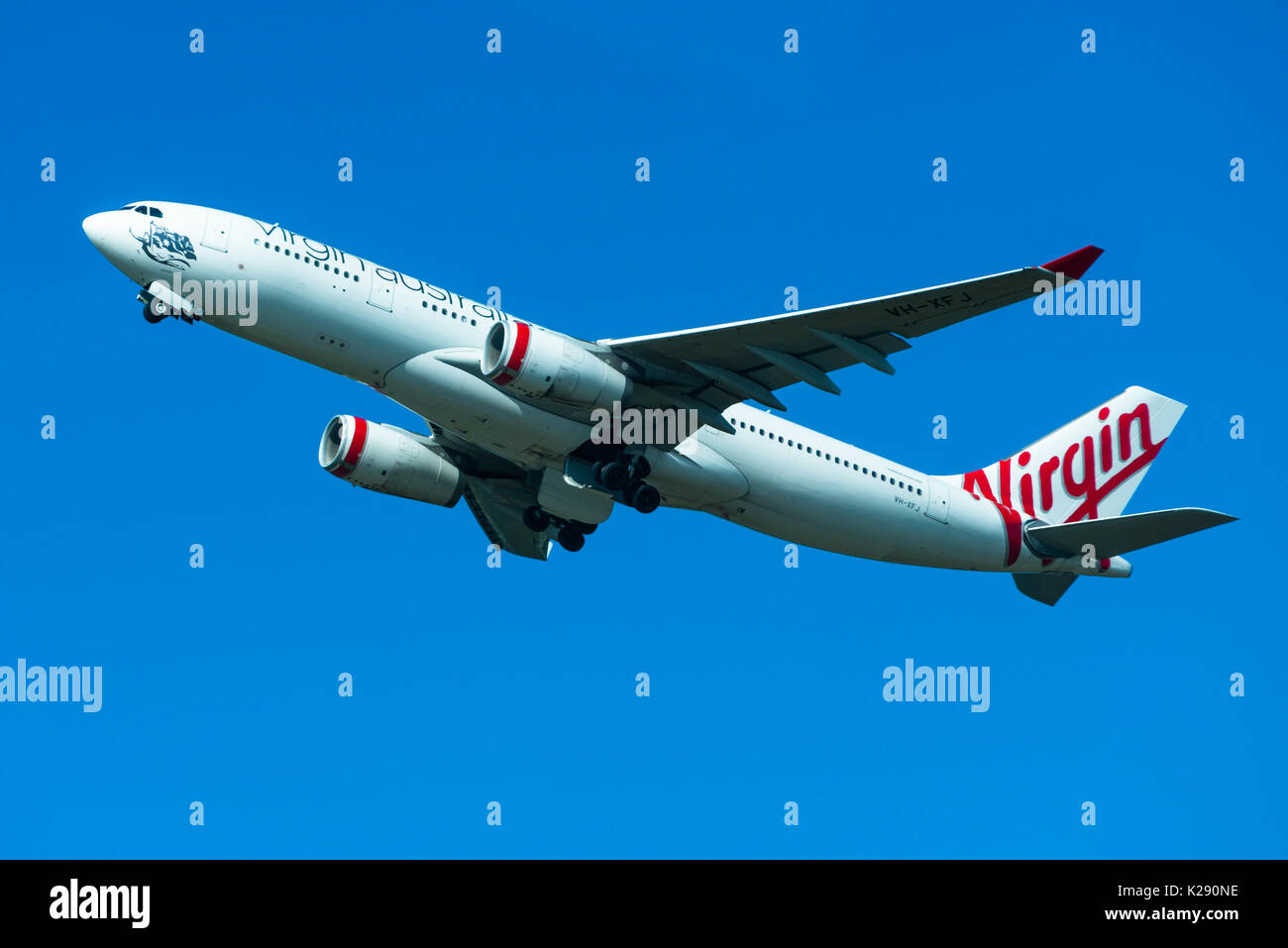 Virgin Australia passenger airplane taking off from Sydney International Airport, New South Wales, Australia. - Stock Image