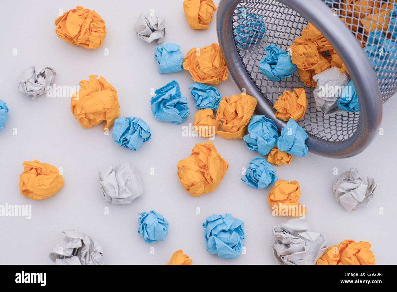 Colorful crumpled paper balls rolling out of a trash can. Idea Concept. - Stock Image