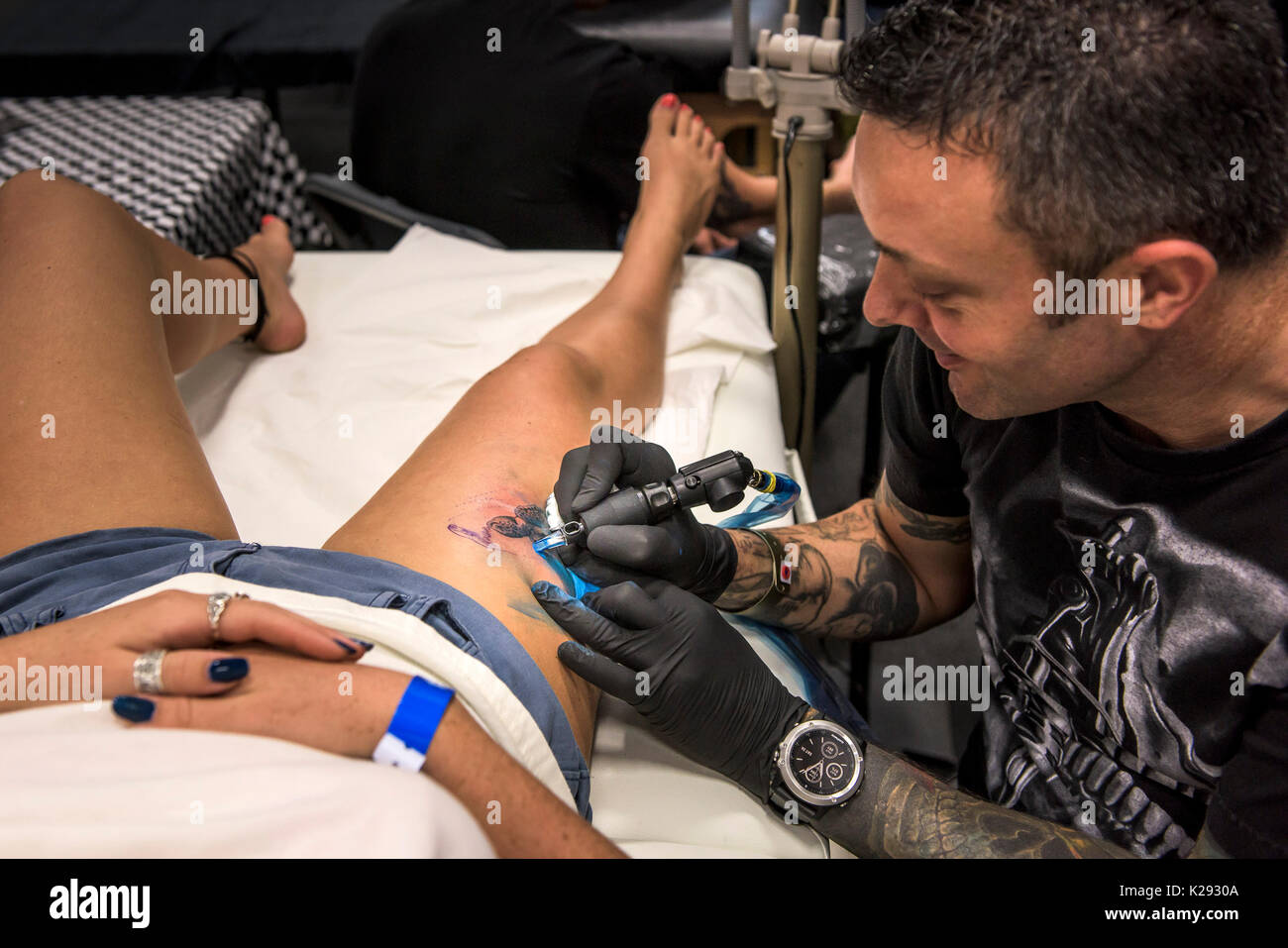 Tattoo - Mark Breed tattooing a design on the thigh of a female customer at the Cornwall Tattoo Convention. - Stock Image